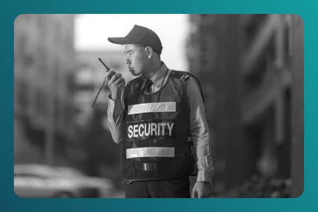 Security guard speaking into portable radio
