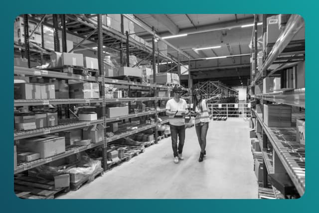 Two warehouse workers walking in distribution storage area